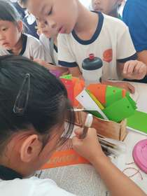 Pupils using recycles paper to make bookmarks.jpg